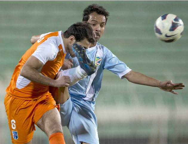 Al Salmiya's Ajab fights for the ball with Kazma's Barakat during their Kuwaiti Premier League soccer match in Kuwait City
