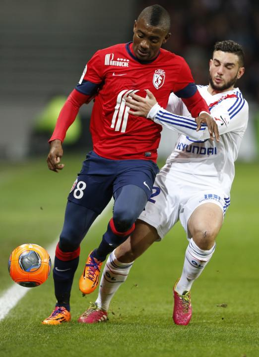 Lille's Kalou challenges Lyon's Ferri for the ball during their French Ligue 1 soccer match at Pierre Mauroy Stadium in Villeneuve d'Ascq