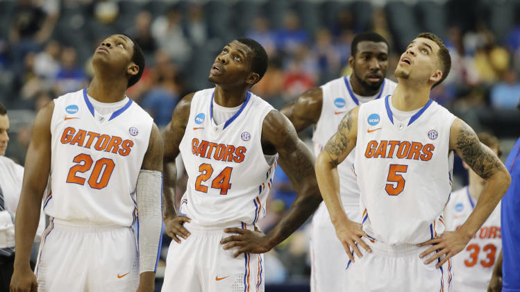 Florida players Michael Frazier II (20), Casey Prather (24) and Scottie Wilbekin (5) watch the big screen during the first half of a regional final game against Michigan  in the NCAA college basketball tournament, Sunday, March 31, 2013, in Arlington, Texas. (AP Photo/David J. Phillip)