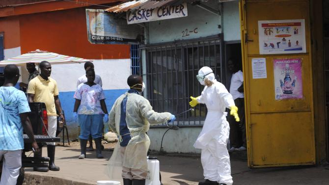 A member of a burial team sprays a colleague with chlorine disinfectant in Monrovia