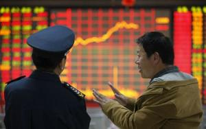 An investor talks to a security guard in front of an electronic board showing stock information at a brokerage house in Huaibei