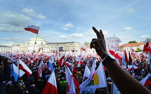 <p>Demonstrators hold Polish national flags during an opposition rally in Warsaw.</p>