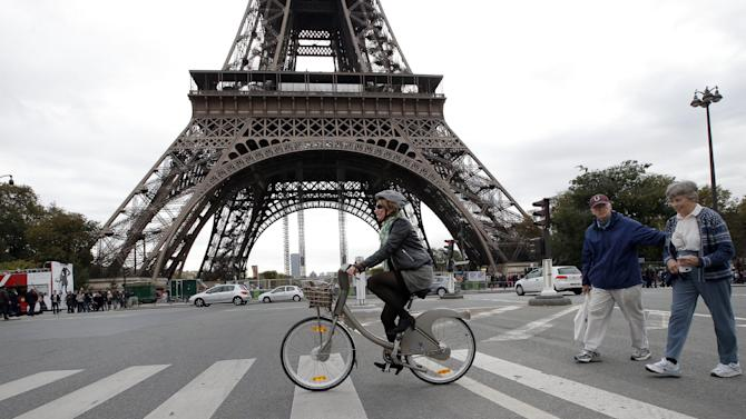 "A woman rides a Velib bike-sharing program closed to the Eiffel Tower, seen in background, in Paris, Tuesday, Oct. 30, 2012. From London's ""cycle superhighways"" to popular bike-sharing programs in Paris and Barcelona, growing numbers of European cities are embracing cycling as a safe, clean, healthy, inexpensive and even trendy way to get around town. (AP Photo/Francois Mori)"