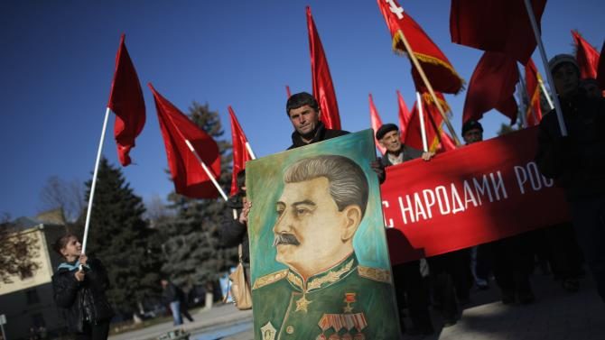 People march with red Soviet flags and portrait of Soviet dictator Josef Stalin during a rally marking Stalin's birthday anniversary of at his hometown in Gori