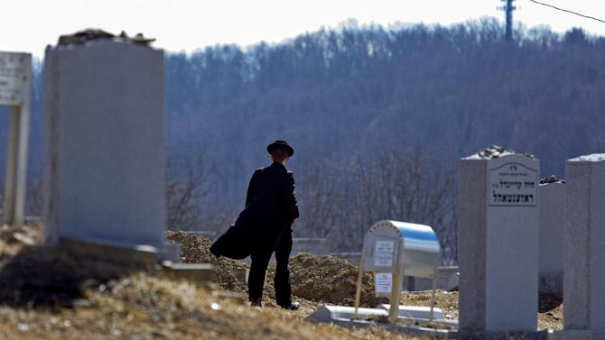 A person walks towards the graves of Nathan and Raizy Glauber, at the Satmar Cemetery 2 in Kiryas Joel, New York, Monday, March 4, 2013.  The baby boy delivered prematurely after his parents, Nathan and Raizy Glauber, were killed Sunday in a New York City hit-and-run accident died Monday, March 4, 2013, a community spokesman said, while the search for the driver who fled on foot narrowed. (AP Photo/Craig Ruttle)