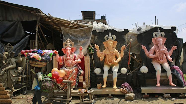 A vendor carries plastic goods and walks past idols of elephant-headed Hindu god Ganesha kept on display for sale ahead of Ganesha Chaturthi festival in Gauhati, India, Wednesday Aug. 27, 2014. Ganesha Chaturthi, the 10-day festival that celebrates the birth of Ganesha, begins Aug. 29 and ends with the immersion of Ganesha statues in the Arabian Sea and other water bodies.(AP Photo/Anupam Nath)