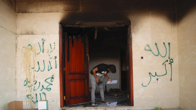 """FILE - In this Wednesday, Sept. 12, 2012 file photo, a man looks at documents at the U.S. consulate in Benghazi, Libya, after an attack that killed four Americans, including Ambassador Chris Stevens. The graffiti reads, """"no God but God,""""  """" God is great,"""" and """"Muhammad is the Prophet."""" CIA security officers went to the aid of State Department staff less than 25 minutes after they got the first call for help during the attack on the U.S. Consulate in Benghazi, Libya, U.S. intelligence officials said Thursday, Nov. 1, 2012, as they laid out a detailed timeline of the CIA's immediate response to the attack from its annex less than a mile from the diplomatic mission.(AP Photo/Ibrahim Alaguri)"""