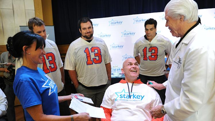 IMAGE DISTRIBUTED FOR STARKEY HEARING FOUNDATION - From left to right in back, Tennessee Titan Craig Stevens, New Orleans Saint Brian de la Puente, actor Lou Ferrigno and Bill Austin, founder of Starkey Hearing Foundation, fits Frankie Ibieta with a new hearing aid on Saturday, Feb. 2, 2013 in New Orleans. (Photo by Cheryl Gerber/Invision for Starkey Hearing Foundation/AP Images)