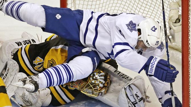 Toronto Maple Leafs right wing Joffrey Lupul, top, bends Boston Bruins goalie Tuukka Rask's head to his leg as he crashes into him while chasing the puck during the second period in Game 7 of their NHL hockey Stanley Cup playoff series in Boston, Monday, May 13, 2013. (AP Photo/Charles Krupa)