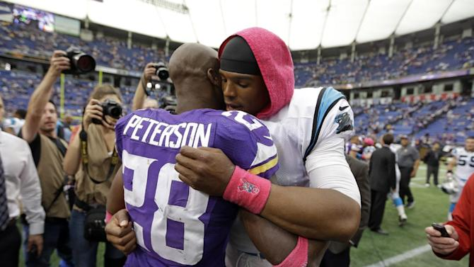 Minnesota Vikings running back Adrian Peterson, left, hugs Carolina Panthers quarterback Cam Newton following a 35-10 Panthers win in an NFL football game in Minneapolis, Sunday, Oct. 13, 2013. One of Peterson's sons, a 2-year-old in South Dakota, died Friday after an alleged attack in a child abuse case