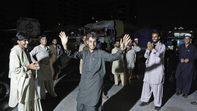 Drivers of oil tankers, which were used to transport NATO fuel supplies to Afghanistan, dance celebrating the news that Pakistan will reopen NATO supply routes, in Karachi, Pakistan, Tuesday, July 3, 2012. The Obama administration said Tuesday that Pakistan was reopening its supply lines into Afghanistan, after the U.S. belatedly issued an apology for the November killing of 24 Pakistani troops in a NATO airstrike. (AP Photo/Shakil Adil)