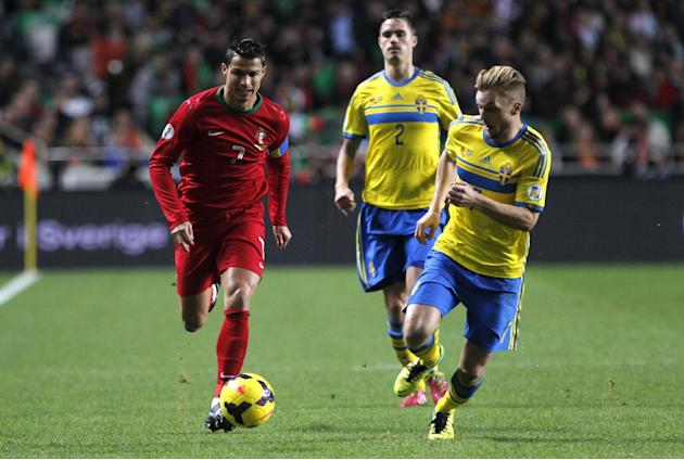 Portugal's Cristiano Ronaldo, left, chases the ball with Sweden's Sebastian Larsson, right, during a World Cup qualifying first leg playoff soccer match between Portugal and Sweden at the Luz stadium