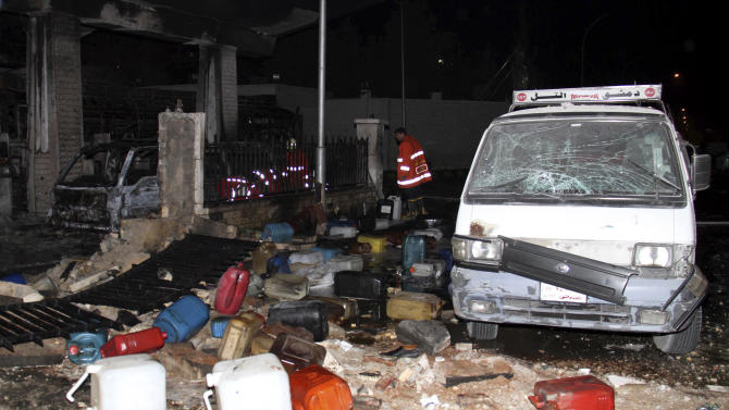 In this photo released by the Syrian official news agency SANA on Thursday, Jan. 3, 2013, Syrian firefighters check a gas station that was attacked by a car bomb killing several people, activists said, in Damascus, Syria. Syrian ground and air forces bombarded rebel strongholds on the outskirts of Damascus and other areas around the country Friday while anti-government forces targeted a military post near the capital with a car bomb, activists said. (AP Photo/SANA)