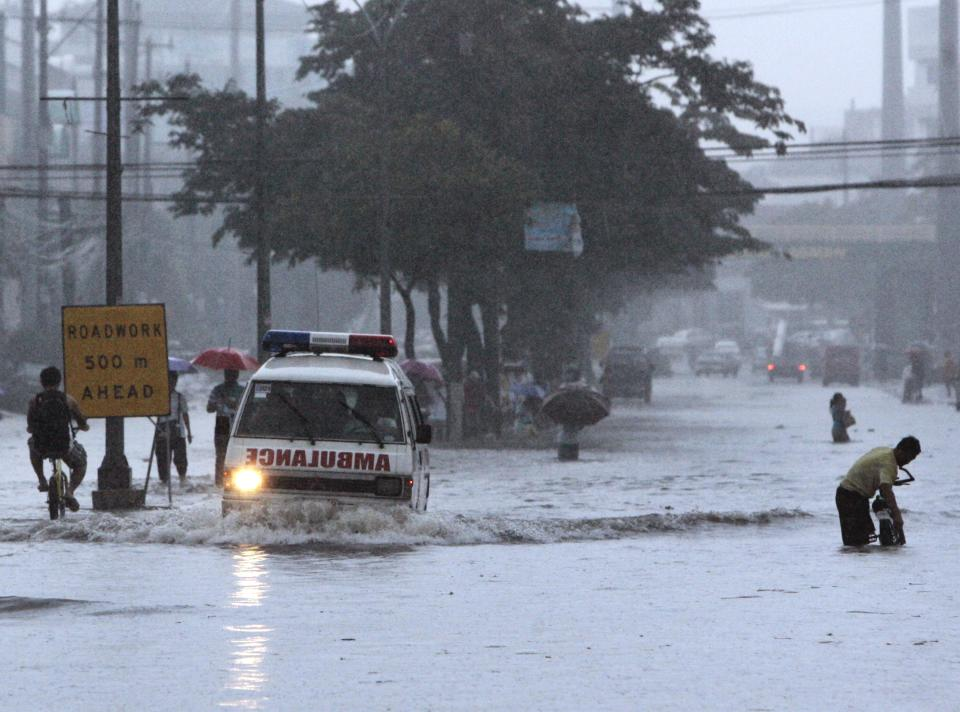 Am ambulance negotiates a flooded street Tuesday, Aug. 2, 2011 in suburban Quezon City, north of Manila, Philippines. Waist-deep floods have swamped the streets in the Philippine capital after a night of monsoon rains closed down schools and government offices. (AP Photo/Pat Roque)