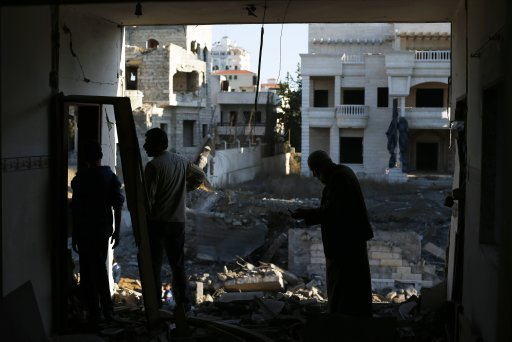 Palestinians check their damaged house after Israeli air strikes in Gaza