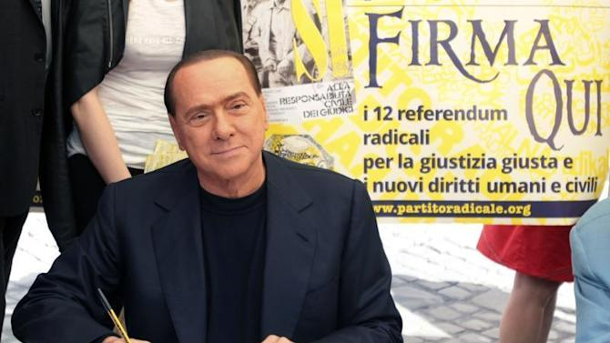 PDL leader Silvio Berlusconi poses as he signs a referendum on justice reforms and human rights in downtown Rome