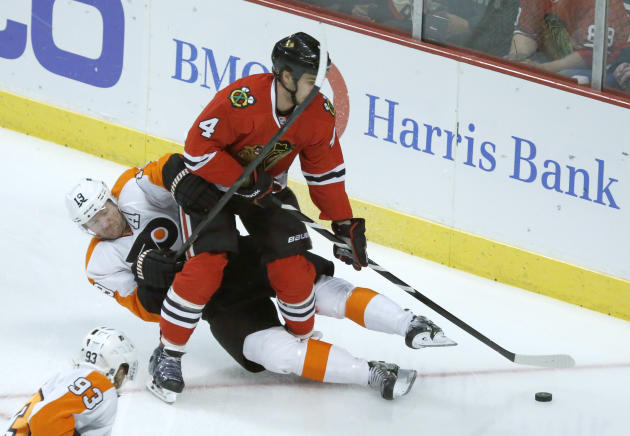Philadelphia Flyers left wing Scott Hartnell (19) battles Chicago Blackhawks defenseman Niklas Hjalmarsson (4) for a loose puck during the first period of an NHL hockey game on Wednesday, Dec. 11, 201