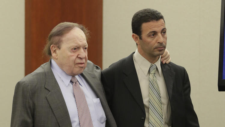 Las Vegas Sands Corp. CEO Sheldon Adelson, left, is assisted into the courtroom before testifying for a second day, Friday, April 5, 2013, in Las Vegas. Attorneys for Hong Kong businessman Richard Suen say Sands owes him $328 million because he worked behind the scenes to help the company win a gambling license in the Chinese enclave of Macau. (AP Photo/Julie Jacobson)