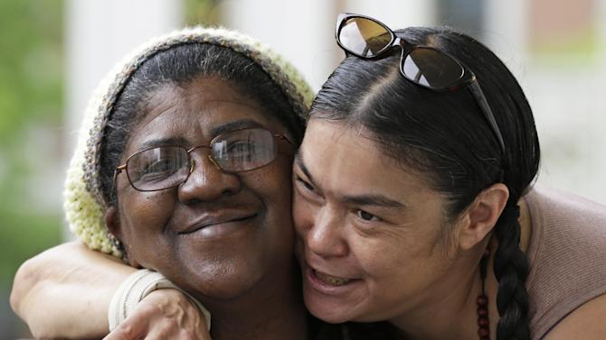 Sherene Julian, right, hugs her friend Robin Howard outside the Anna Louise Inn, in Cincinnati on Thursday, May 16, 2013. The two are residents of the home for struggling women. In a deal with Western & Southern Insurance Group, who bought the 104-year-old inn for $4 million, the women now living there will remain where they are for two years as a new facility for them is built. (AP Photo/Al Behrman)