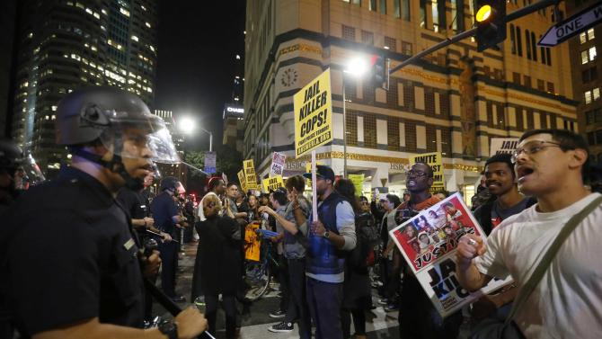 Police face off against protesters as they corral the demonstrators before detaining them during a march in Los Angeles
