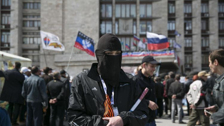 A masked pro-Russian man stand guard near a barricade outside a regional government building in Donetsk, eastern Ukraine