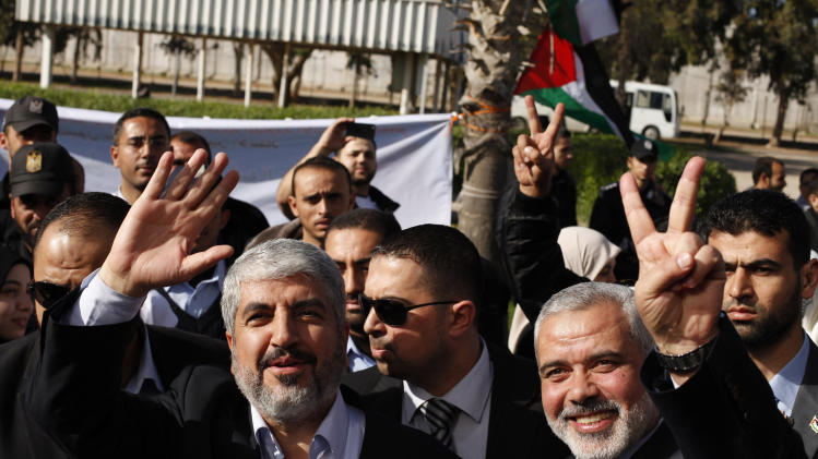Exiled Hamas chief Khaled Mashaal, left, and Gaza's Hamas Prime Minister Ismail Haniyeh upon Meshaal's arrival at Rafah crossing in the southern Gaza Strip, Friday, Dec. 7, 2012. The exiled Hamas chief broke into tears Friday as he arrived in the Gaza Strip for his first-ever visit, a landmark trip reflecting his militant group's growing international acceptance and its defiance of Israel. Khaled Mashaal, who left the West Bank as a child and leads the Islamic militant movement from Qatar, crossed the Egyptian border, kissed the ground, and was greeted by a crowd of Hamas officials and representatives of Hamas' rival Fatah party. He was also welcomed by a group of Palestinian orphans — children of Gaza militants killed by Israel in recent years — wearing military-style uniforms. (AP Photo/Suhaib Salem, Pool)