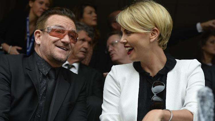 U2's lead singer Bono and actress Charlize Theron attend the memorial service of South African former president Nelson Mandela at the FNB Stadium (Soccer City) in Johannesburg on December 10, 2013