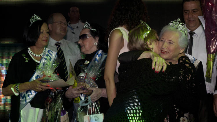 "Hava Hershkovitz, right, a Holocaust survivor and winner of a beauty pageant is congratulated by another participant, in the northern Israeli city of Haifa, Thursday, June 28, 2012. Fourteen women who lived through the horrors of World War II paraded on stage Thursday night in an unusual pageant, vying for the honor of being Israel's first ""Miss Holocaust Survivor."" (AP Photo/Sebastian Scheiner)"