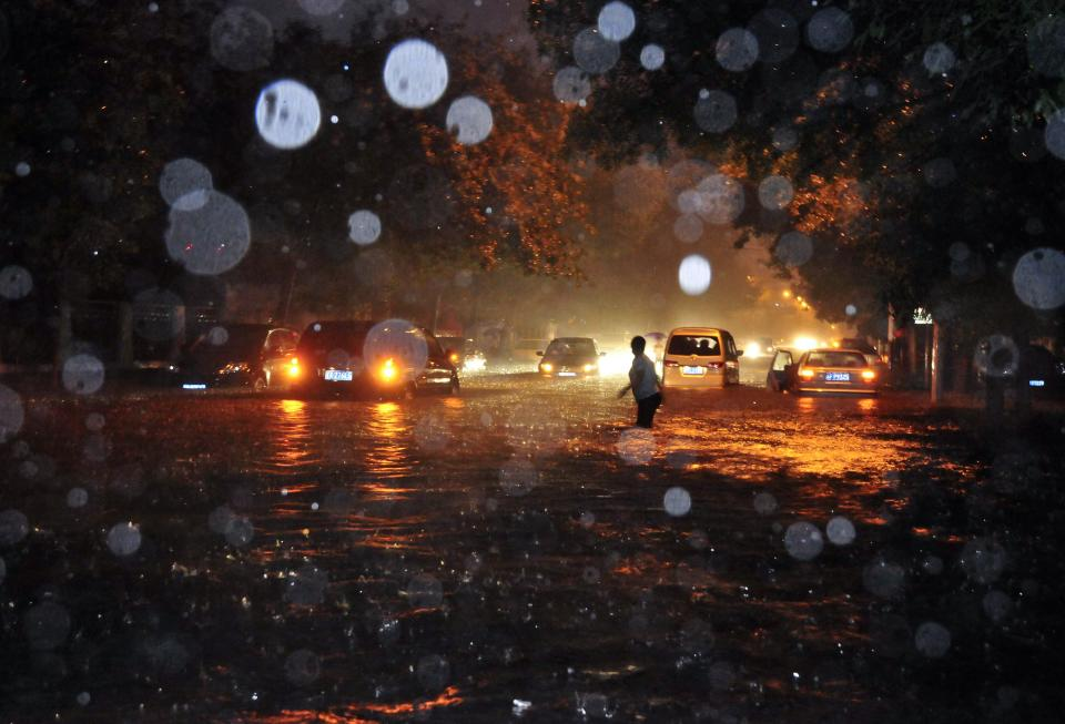 A woman wades through a flooded street following a heavy rain in Beijing Saturday, July 21, 2012. China's government says the heaviest rains to hit Beijing in six decades. The torrential downpour Saturday night left low-lying streets flooded and knocked down trees. (AP Photo) CHINA OUT