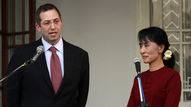 In this photo taken on March 14, 2012, Derek Mitchell, left,  then U.S special envoy to Myanmar, speaks during a press conference after meeting with opposition leader Aung San Suu Kyi, right, at her residence in Yangon, Myanmar.  The U.S. Embassy in Myanmar says Mitchell, Washington's first ambassador to the Southeast Asian nation in 22 years has arrived.  Embassy spokeswoman Adrienne Nutzman says Mitchell flew into the main city, Yangon, on Wednesday, July 11,  and will formally present his credentials to President Thein Sein in the capital Naypyitaw. (AP Photo/Khin Maung Win)