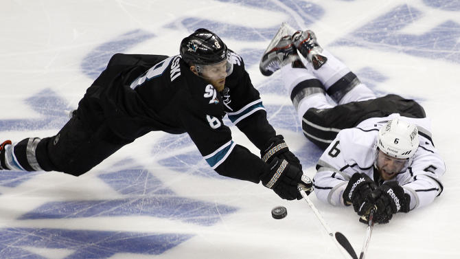 San Jose Sharks center Joe Pavelski (8) battles for a puck against Los Angeles Kings defenseman Jake Muzzin (6) during the third period in Game 6 of their second-round NHL hockey Stanley Cup playoff series in San Jose, Calif., Sunday, May 26, 2013. San Jose won 2-1. (AP Photo/Tony Avelar)