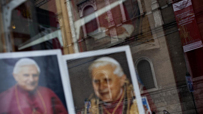 A nun is reflected in a shop window with portraits of Pope Benedict XVI, in Rome, Monday, Feb. 25, 2013. Pope Benedict XVI has changed the rules of the conclave that will elect his successor, allowing cardinals to move up the start date if all of them arrive in Rome before the usual 15-day transition between pontificates. Benedict signed a legal document, issued Monday, with some line-by-line changes to the 1996 Vatican law governing the election of a new pope. It is one of his last acts as pope before resigning Thursday. (AP Photo/Oded Balilty)
