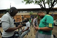 Members of the media wait to see South African Olympic sprinter Oscar Pistorius outside a Pretoria Police Station from about 5am on February 25, 2013. Pistorius met South African probation officers on Monday and discussed conditions to restart training as he awaits trial for the murder of his girlfriend, a prisons spokesman said