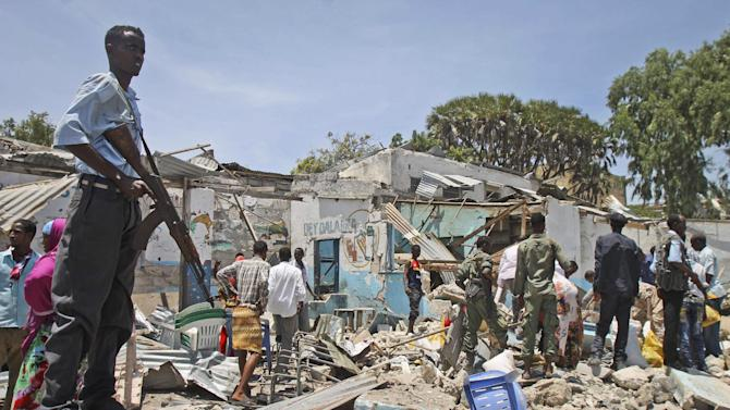 A Somali soldier stands guard near destroyed shops after a car bomb blast close to the Somali government's headquarters in the capital Mogadishu, Somalia Monday, March 18, 2013. An explosives-laden car that apparently was targeting a truck full of Somali government officials instead hit a civilian car and exploded, setting a nearby mini-bus on fire and killing at least seven people Monday, police and witnesses said. (AP Photo/Farah Abdi Warsameh)