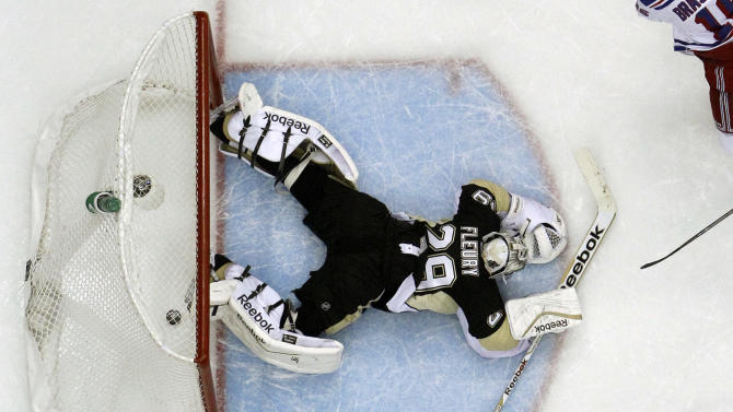 Pittsburgh Penguins goalie Marc-Andre Fleury (29) lies in the goal crease with the puck behind him after allowing a goal to New York Rangers' Derick Brassard in the first period of Game 5 of a second-round NHL playoff hockey series in Pittsburgh, Friday, May 9, 2014. The Rangers won 5-1. (AP Photo/Gene J. Puskar)