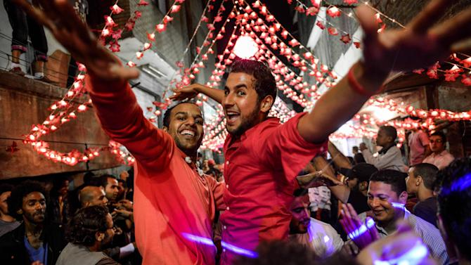 In this Tuesday, April 16, 2013 photo, young Egyptian men dance at a wedding party in Cairo, Egypt. Egypt's economy has been hard hit by the two years of turmoil that followed the ouster of longtime President Hosni Mubarak. Half of the country's 85 million people live at or below the poverty line of $2 a day and rely on government subsidies of wheat and fuel for survival.(AP Photo/Eman Helal)