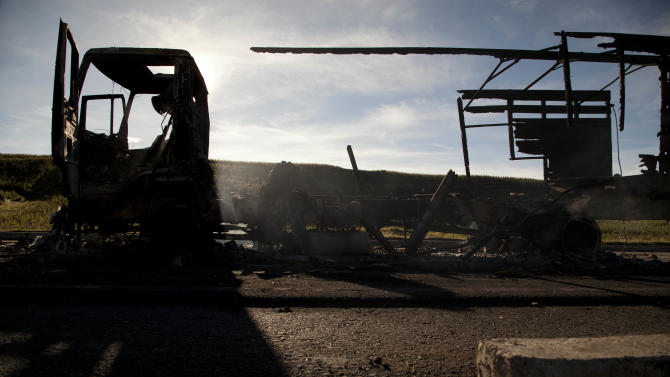 In this Oct. 5, 2012 photo, the shell of a a torched army truck sits at the scene where protestors from Totonicapan and soldiers clashed a day earlier on the outskirts of Santa Catarina Ixtahuacan, near Totonicapan, Guatemala. Experts said the arrest of soldiers in connection with the Oct. 4 killing of Indians protesting high electricity prices mark a dramatic shift in a country once known for its reluctance to punish its military. (AP Photo/Moises Castillo)