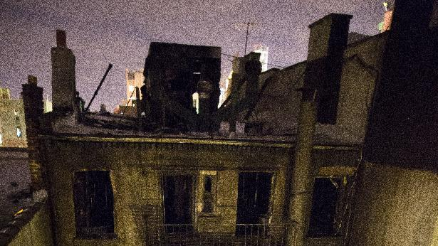 A firefighter enters the rear of 41 Spring Street in lower Manhattan after it was engulfed in a five alarm fire that had been contained, Thursday, Jan. 10, 2013, in New York. One person has died and eight people were injured. (AP Photo/John Minchillo)
