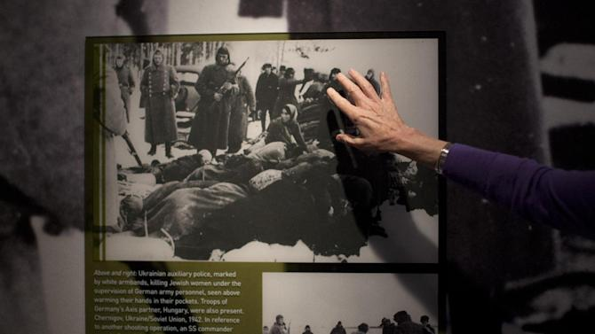 """In this Thursday, April 25, 2013 photo, United States Holocaust Memorial Museum curator Susan Bachrach points out a 1942 photo of Ukrainian auxiliary police killing Jewish women under the supervision of German army personnel and in the presence of Hungarian troops during a preview of the new exhibit """"Some Were Neighbors: Collaboration & Complicity in the Holocaust"""" in Washington. The exhibition, opening April 30, 2013, includes interviews with perpetrators of collaboration and complicity in the Nazi genocide. (AP Photo/Carolyn Kaster)"""