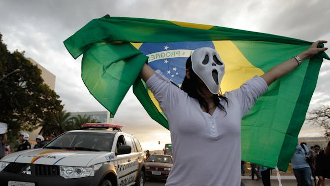 A demonstrator wearing a mask holds a Brazilian flag during a protests in front of the Brazilian National Congress in Brasilia, Brazil, Monday, June 17, 2013. Protesters massed in at least seven Brazilian cities Monday for another round of demonstrations voicing disgruntlement about life in the country, raising questions about security during big events like the current Confederations Cup and a papal visit next month. (AP Photo/Eraldo Peres)