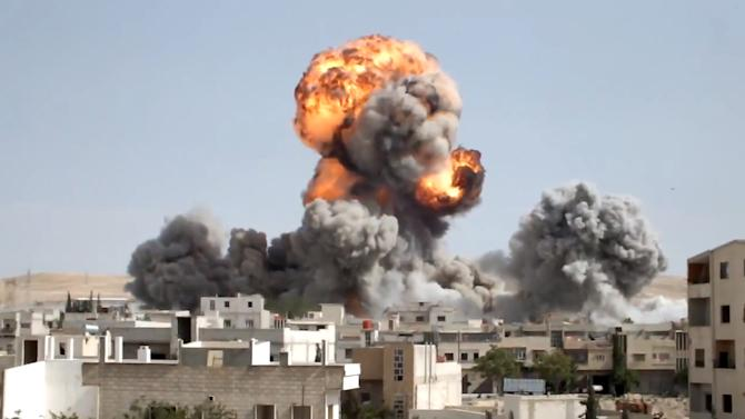 In this image taken from video obtained from the Shaam News Network, which has been authenticated based on its contents and other AP reporting, smoke and fire rises after explosives were dropped by a Syrian government warplane in Yabroud near Damascus, Syria, Monday May 20, 2013. The Syrian regime claims there is no civil war in the country but that the army is fighting foreign-backed terrorists trying to topple Assad's government. More than 70,000 people have been killed in Syria since March 2011. (AP Photo/Shaam News Network via AP video)