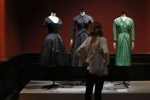 "A visitor looks at vintage dresses by designers Christian Dior, Jacques Heim and Givenchy presented in the exhibition ""Les Annees 50, La mode en France"" at the Palais Galliera fashion museum in Paris"
