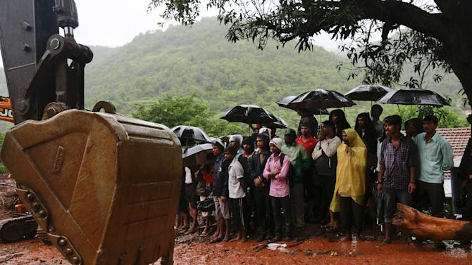 Indian villagers watch rescue operations at the site of a massive landslide in Malin village in Pune district of western Maharashtra state, India, Thursday, July 31, 2014. Two days of torrential rains triggered the landslide early Wednesday, killing more than two dozen people and trapping more than 150, authorities said. (AP Photo/Rafiq Maqbool)