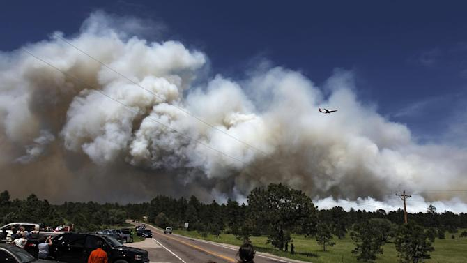 People pulled to over watch from their cars as a fire-fighting slurry plane makes a pass in preparation to drop its load on a wildfire in the Black Forest area north of Colorado Springs, Colo., on Wednesday, June 12, 2013. The number of houses destroyed by the Black Forest fire could grow to around 100, and authorities fear it's possible that some people who stayed behind might have died. (AP Photo/Brennan Linsley)