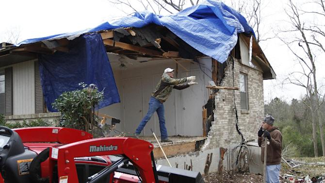 Michael Donaldson, left, and Michael Lane work on clearing away damage done to the home of John Templeton in Centreville, Miss. on Wednesday, Dec. 26, 2012. Templeton said there were four people at home at the time of the storm, all were unharmed after seeking shelter in the basement. More than 25 people were injured and at least 70 homes were damaged in Mississippi by the severe storms that pushed across the South on Christmas Day, authorities said Wednesday. (AP Photo/The Enterprise-Journal, Philip Hall)