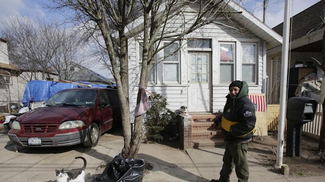 Eddie Saman walks to his home, Wednesday, Jan. 23, 2013 in the borough of Staten Island in New York. The house was badly damaged by Superstorm Sandy and will have to be renovated. Meanwhile, because of the extreme cold weather, Saman has been spending the night in a tent nearby operated by the volunteer group Cedar Grove Community Hub.  A cold wave with sub-zero temperatures is expected to keep its icy grip on much of the eastern U.S. into the weekend before seasonable temperatures bring relief.(AP Photo/Mark Lennihan)