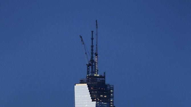 FILE - In this file photo of April 26, 2013, from Bayonne, N.J., One World Trade Center rises behind the Statue of Liberty in New York. It is already New York's tallest building. But when the last pieces of its spire go up to the roof Monday, April 28, the 104-floor skyscraper will be one step away from becoming the highest in the Western Hemisphere. (AP Photo/Mark Lennihan, File)