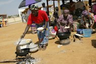 Women cook a bean cake at a mock market in Nigeria in 2003. A UN-linked body launched a campaign in Nigeria on Tuesday aimed at preventing deaths due to toxic smoke from rudimentary cookstoves, one of the developing world's worst public health threats. (AFP Photo/Pius Utomi Ekpei)