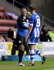 Wigan Athletic manager Owen Coyle with goal scorer Nick Powell after his substitution during the UEFA Europa League match at the DW Stadium, Wigan.