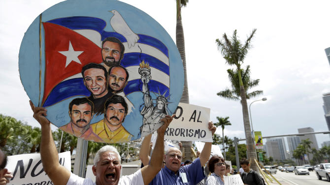Carlos Espinosa, 57, left, holds a sign in support of the Cuban Five, who are serving prison sentences in the U.S., outside of where blogger and activist Yoani Sanchez, of Cuba, speaks at the Freedom Tower of Miami Dade College, Monday, April 1, 2013, in Miami. Sanchez has gained thousands of followers worldwide for her candid descriptions of modern life in Cuba on her blog Generation Y. (AP Photo/Lynne Sladky)